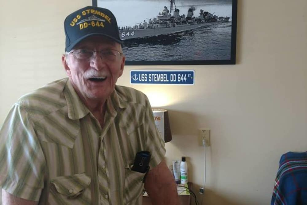 A veteran resident posing in front of a photo of the USS Stembel at Covered Bridge Health Campus in Seymour, Indiana
