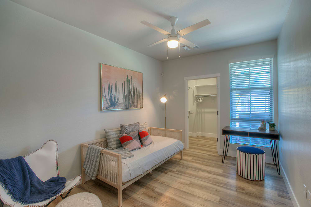 Guest bedroom with ceiling fan and beautiful furnishings in model home at District Lofts in Gilbert, Arizona