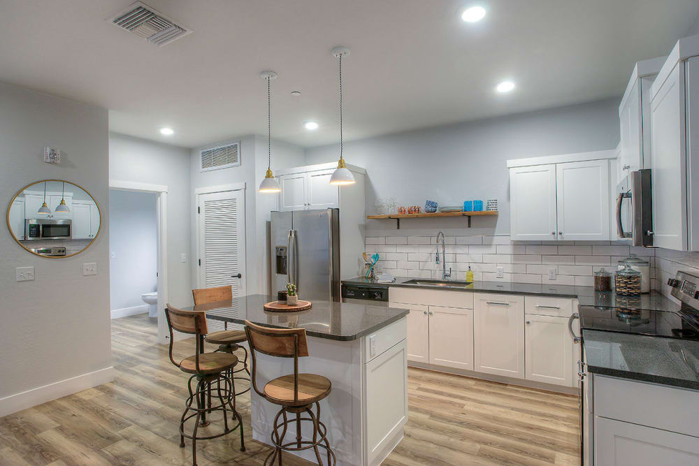 Gourmet kitchen with granite countertops and white cabinetry in model home at District Lofts in Gilbert, Arizona