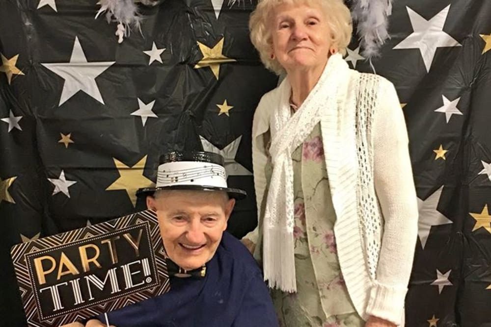 Male and female resident take a party time photo together for theme day at St. Mary Healthcare Center in Lafayette, Indiana