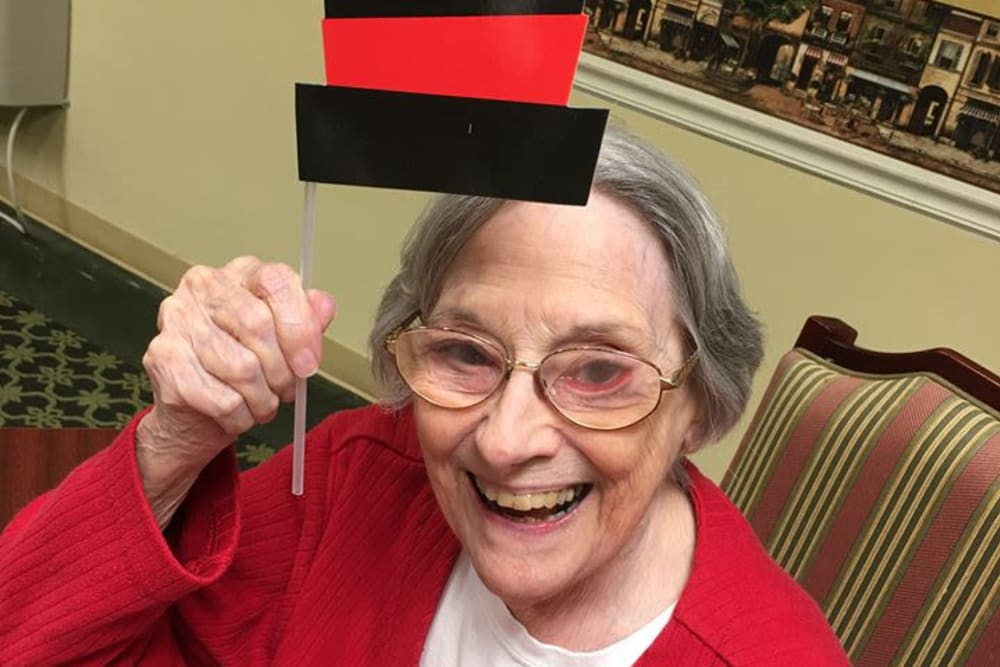 Female resident smiling while holding her paper hat at St. Mary Healthcare Center in Lafayette, Indiana