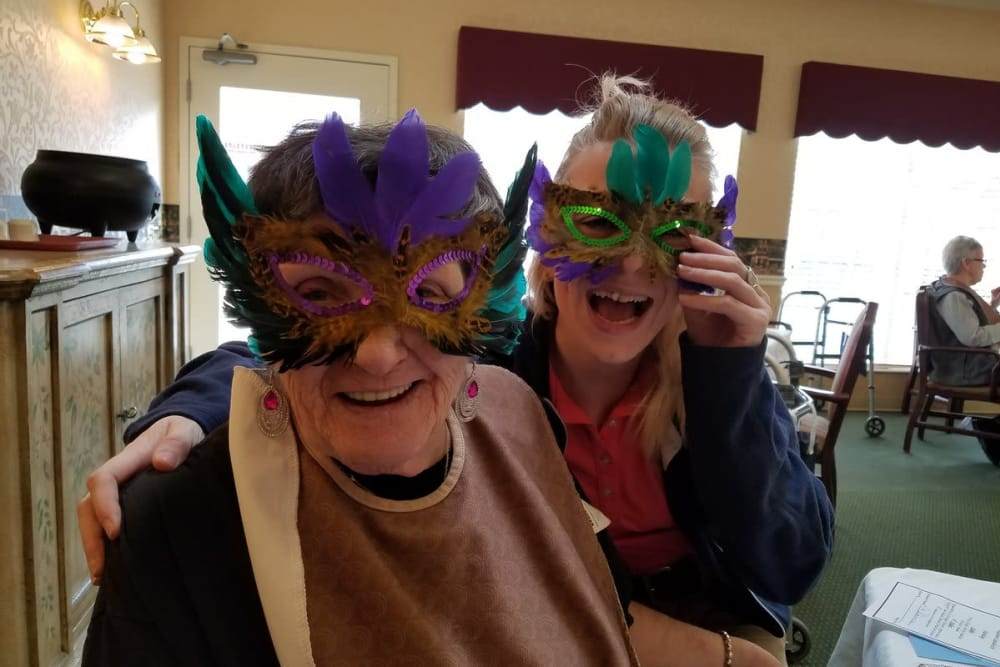 Two female residents wearing colorful feathered masks for theme day at StoneBridge Health Campus in Bedford, Indiana