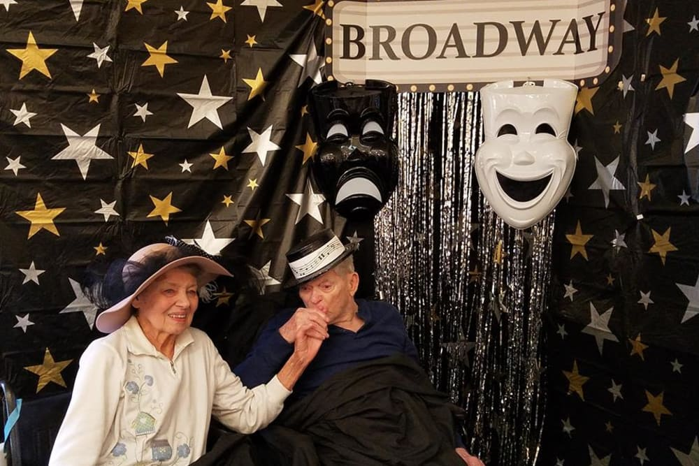 Male resident kissing female residents hand for Broadway theme day photo at StoneBridge Health Campus in Bedford, Indiana