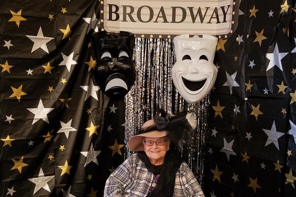 Female resident posing with Broadway backdrop and props for theme day at StoneBridge Health Campus in Bedford, Indiana