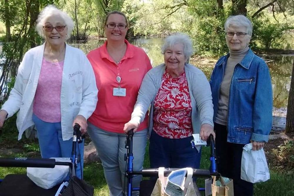 Female residents soaking up the sunshine near a creek at Stonegate Health Campus in Lapeer, Michigan