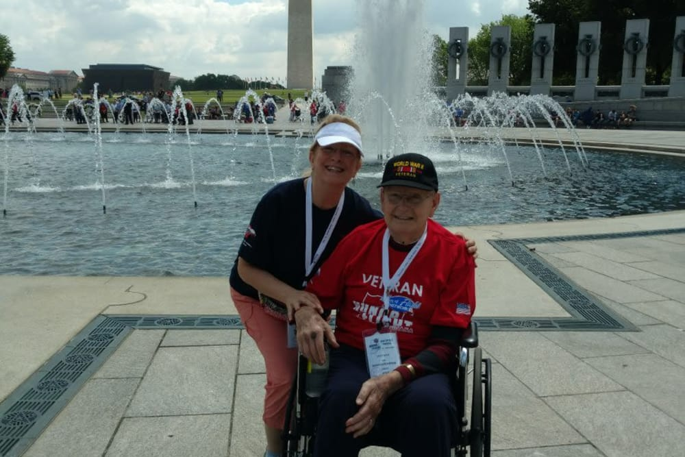 Male veteran and female staff member are smiling in front of a beautiful fountain near Waterford Crossing in Goshen, Indiana