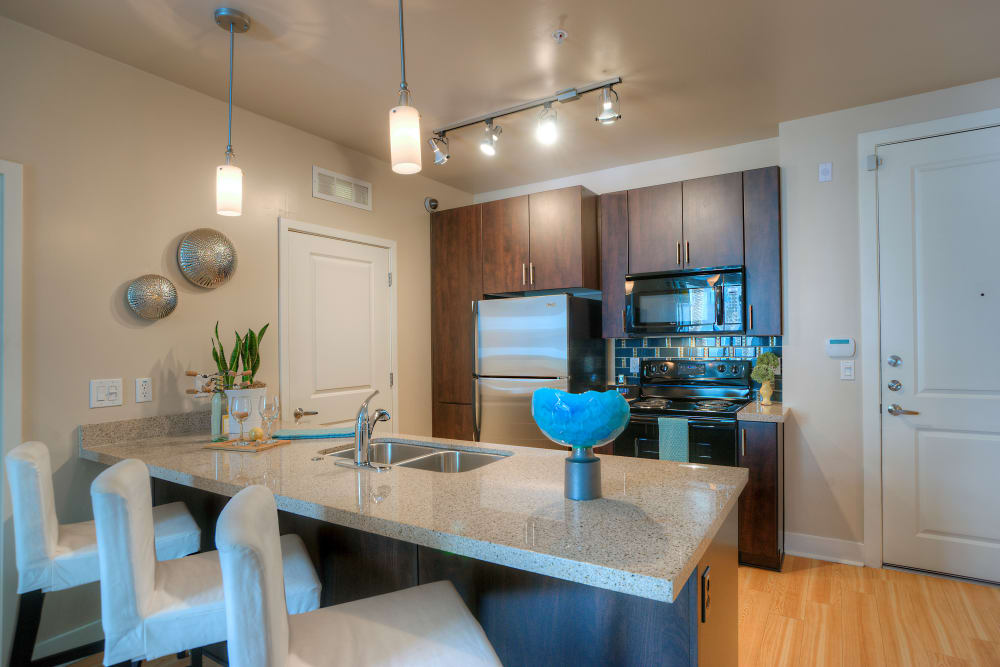 Beautiful gourmet kitchen with breakfast bar and stainless-steel appliances in model home at Level at Sixteenth in Phoenix, Arizona