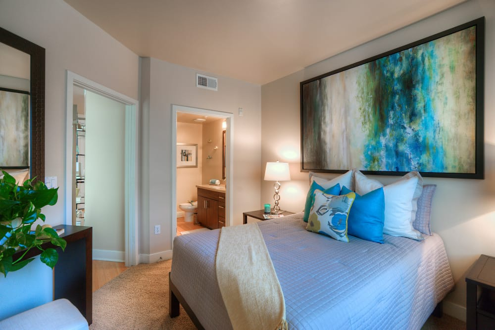 Large master bedroom with beautiful furnishings and en suite bathroom in model home at Level at Sixteenth in Phoenix, Arizona