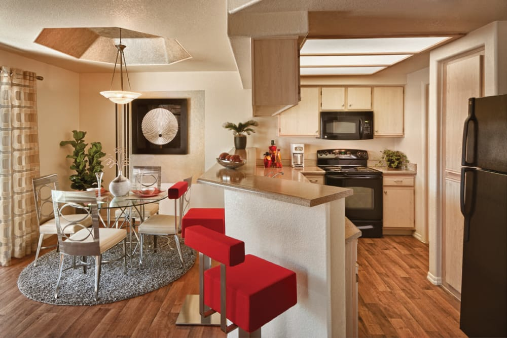 Gourmet kitchen with granite countertops and adjacent dining area in model home at San Palmilla in Tempe, Arizona
