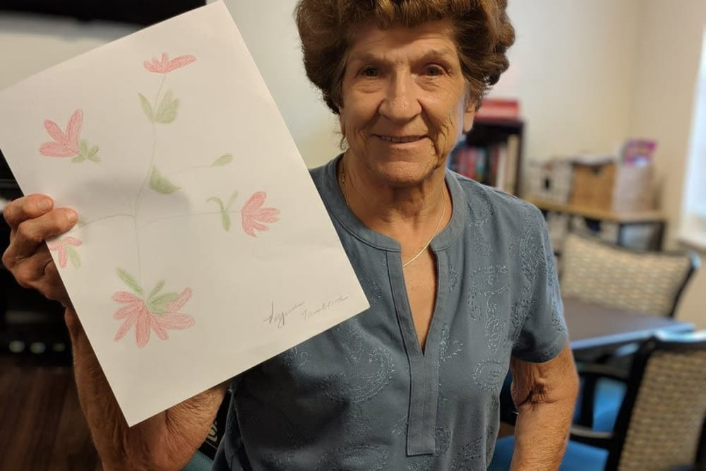 A resident holding up her drawing at Ridgewood Health Campus in Lawrenceburg, Indiana