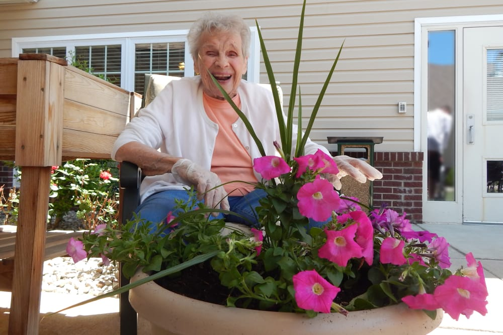 A resident posing for a photo behind flowers at Ridgewood Health Campus in Lawrenceburg, Indiana