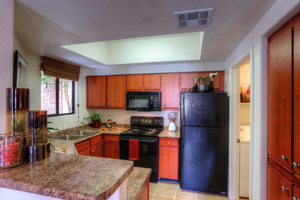 Gourmet kitchen with granite countertops and adjacent workspace in model home at San Marbeya in Tempe, Arizona