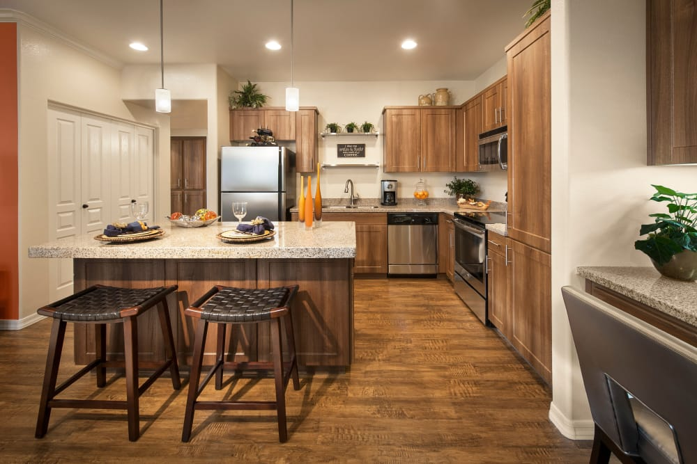 Gourmet kitchen with granite countertops and adjacent workspace in model home at San Capella in Tempe, Arizona