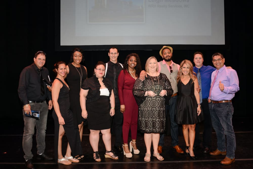 Employees from at WRH Realty Services, Inc stand on stage together