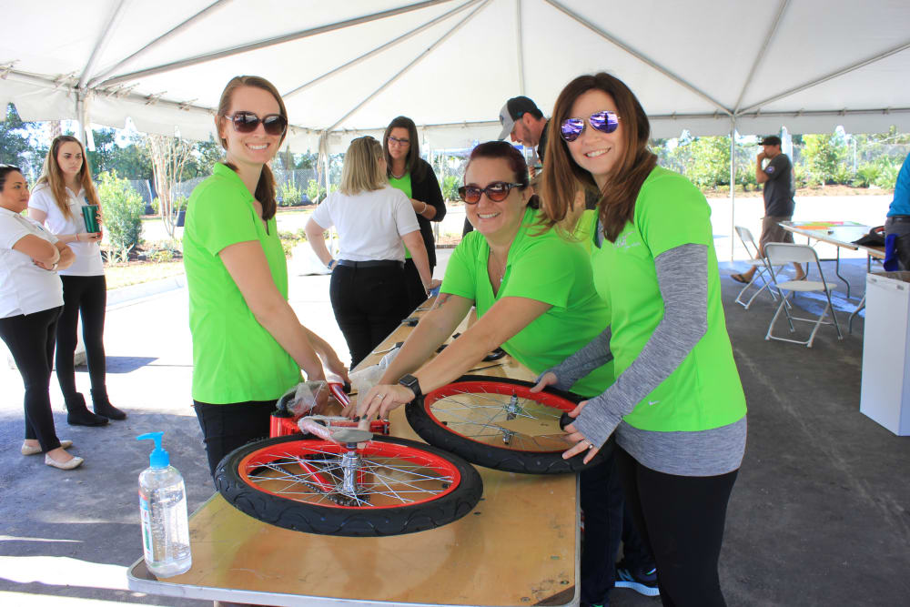 WRH Realty Services, Inc employees present a bicycle they are giving away at a local event