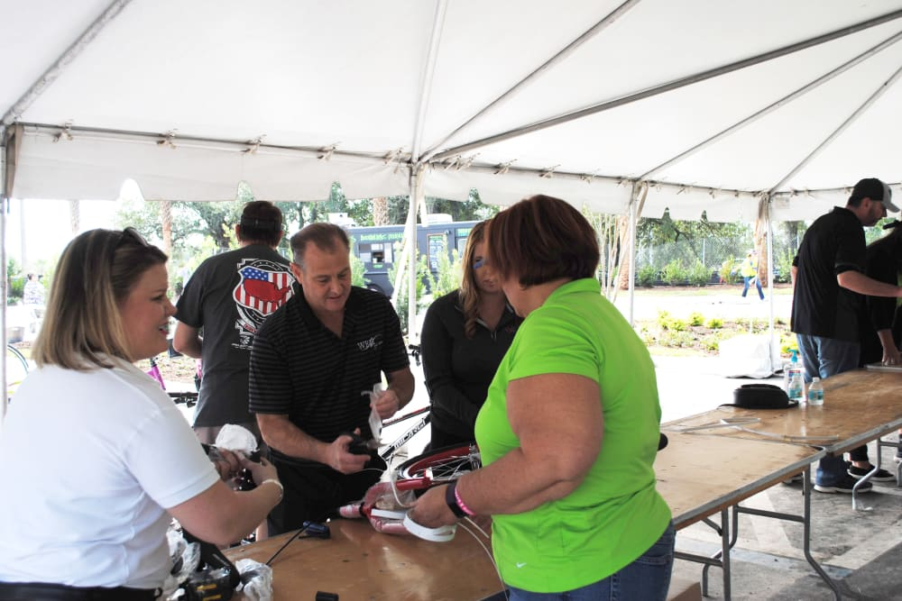 Employees volunteering at a booth for a local event near WRH Realty Services, Inc