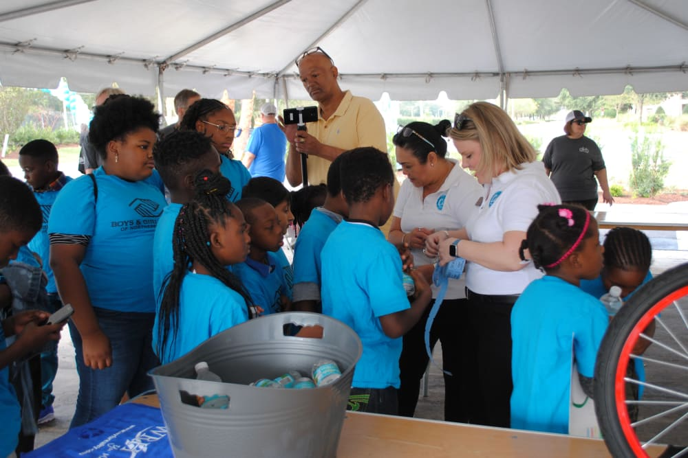 Employees gather with children at a community event near  WRH Realty Services, Inc