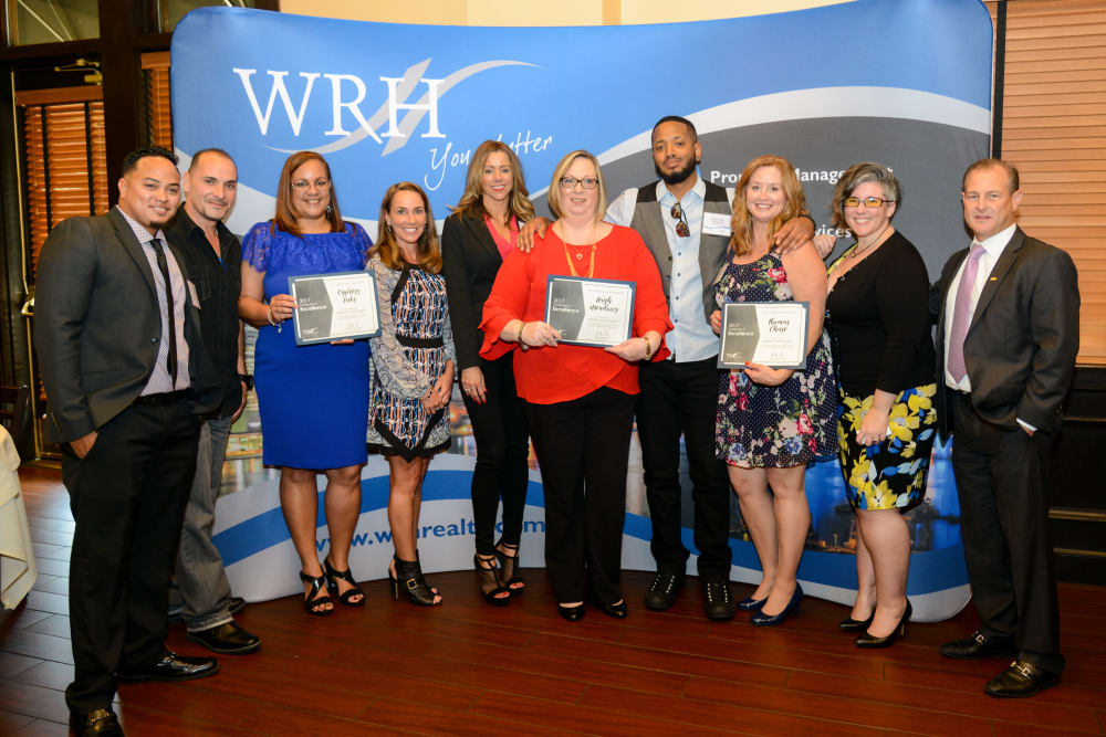 Employees at WRH Realty Services, Inc show off their awards in a group shot