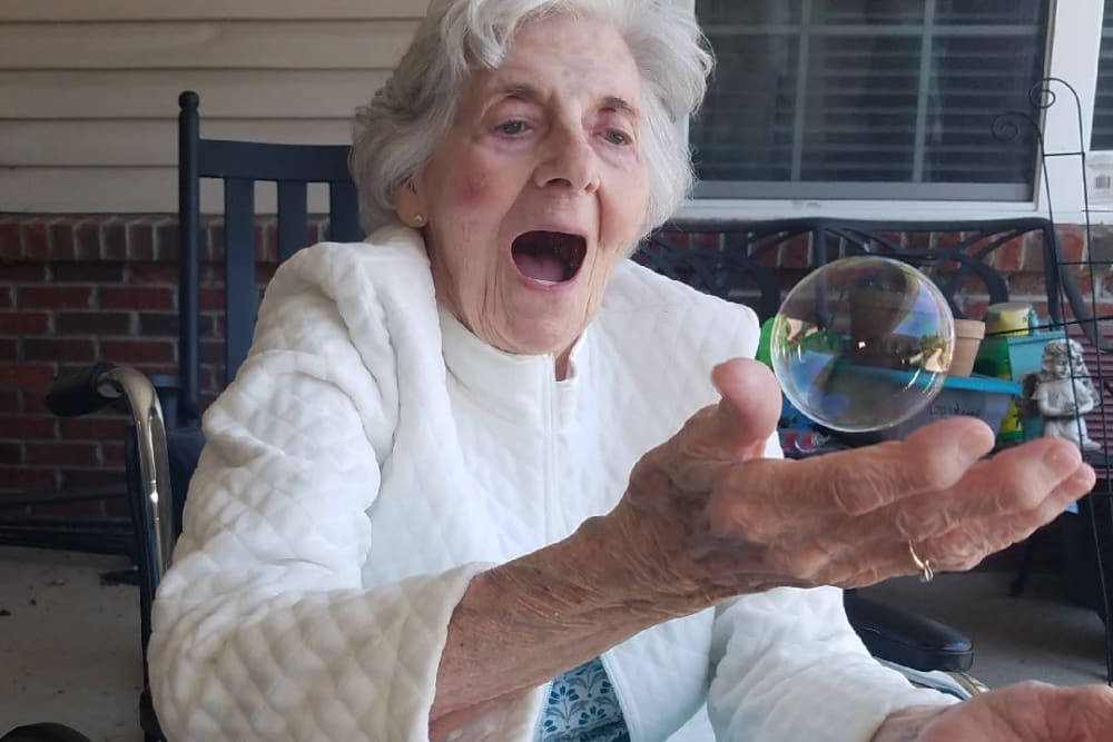 A resident playing with bubbles outside at The Oaks at Northpointe in Zanesville, Ohio