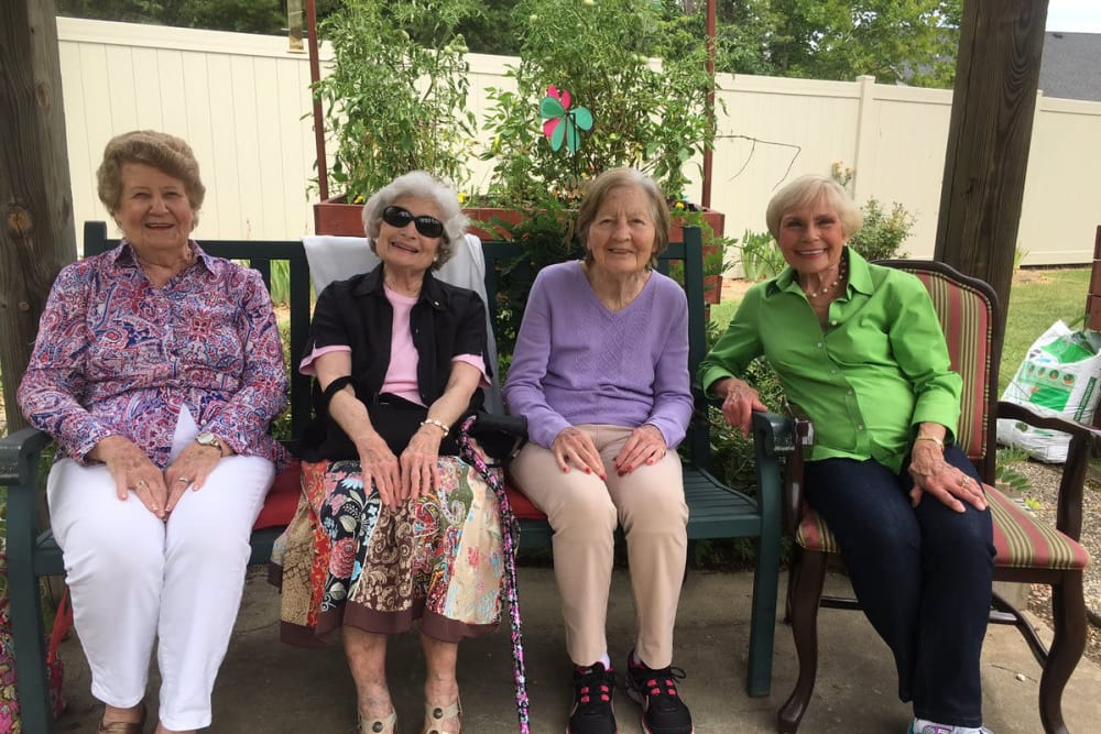 A group of residents sitting on the patio at The Oaks at Woodfield in Grand Blanc, Michigan