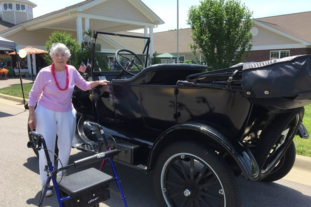 A resident posing by a classic car at The Willows at Hamburg in Lexington, Kentucky