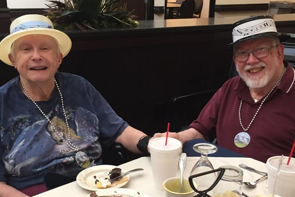 An elderly couple holding hands at a dining table at Novi Lakes Health Campus in Novi, Michigan