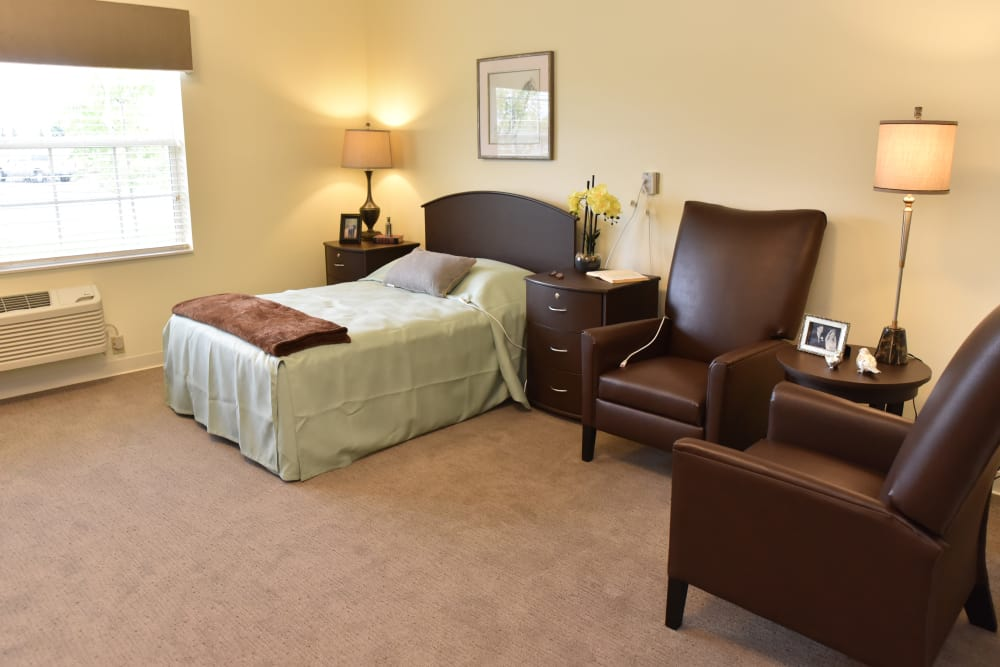 A decorated bed and seating next to it at Orchard Pointe Health Campus in Kendallville, Indiana