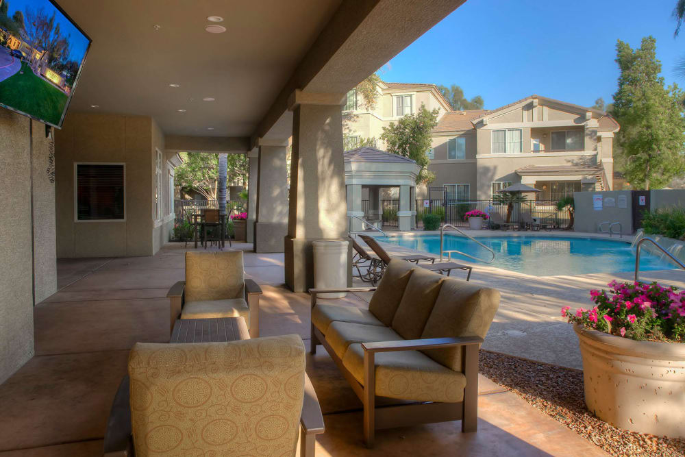 Swimming pool area with covered lounge seating nearby at The Reserve at Gilbert Towne Centre in Gilbert, Arizona