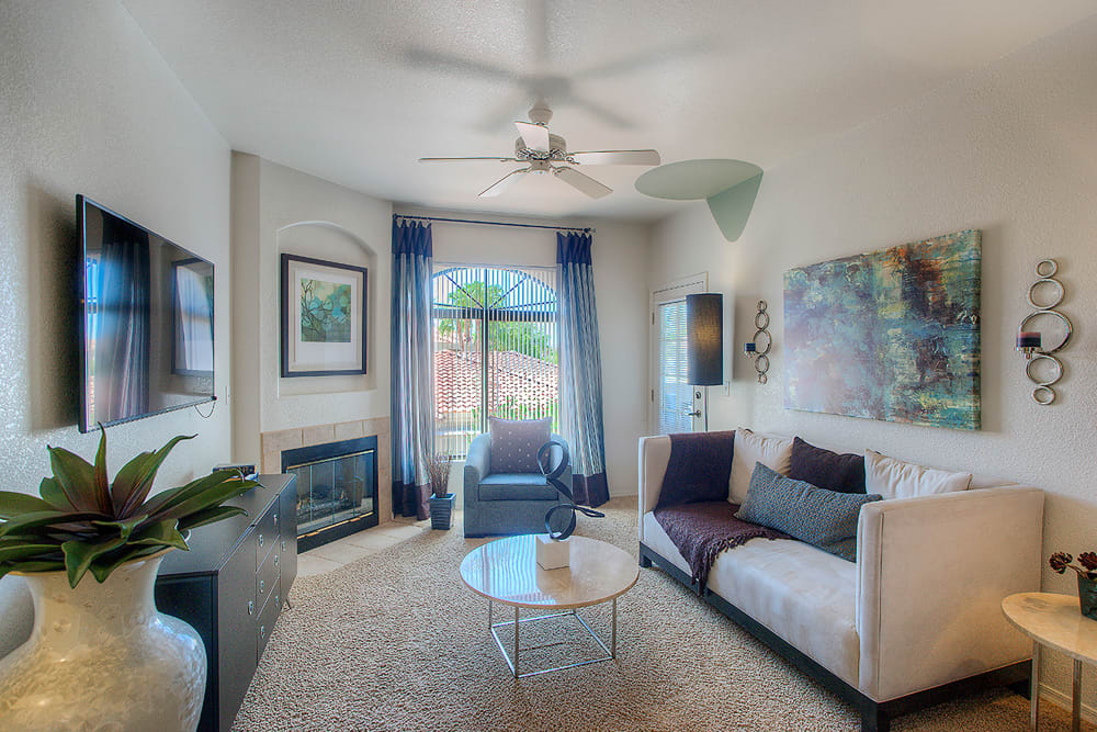 Well-decorated living room with a ceiling fan and plush carpeting in a model home at San Pedregal in Phoenix, Arizona