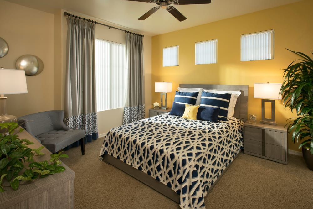 Large master bedroom with ceiling fan and beautiful furnishings in model home at San Valencia in Chandler, Arizona