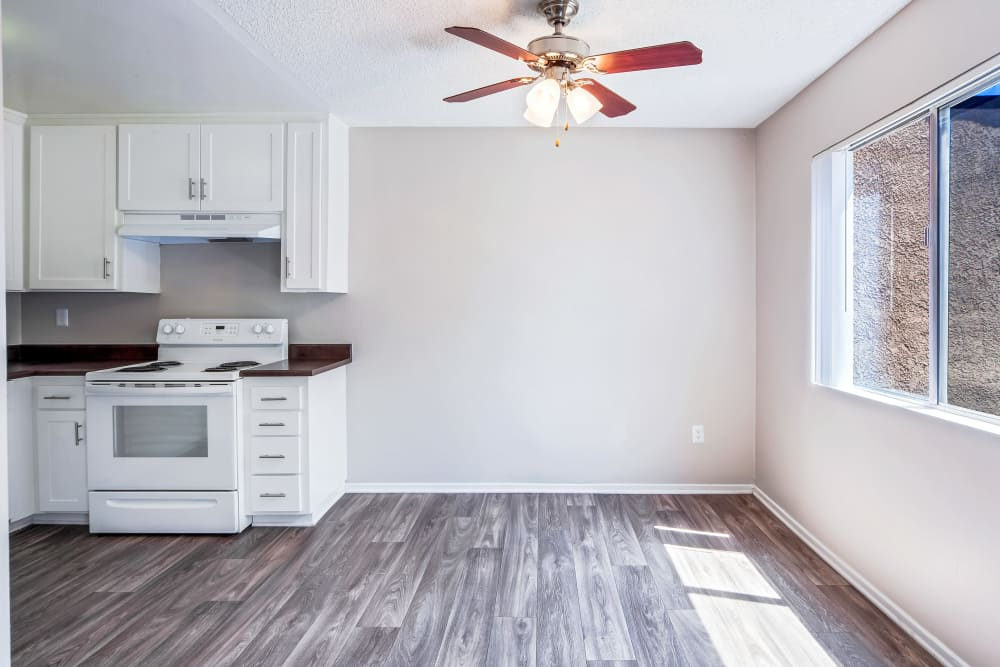 Dining room with ceiling fan and hardwood floors at West Fifth Apartments in Ontario, California