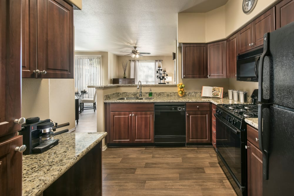 Gourmet kitchen with granite countertops and adjacent workspace in model home at Laguna at Arrowhead Ranch in Glendale, Arizona