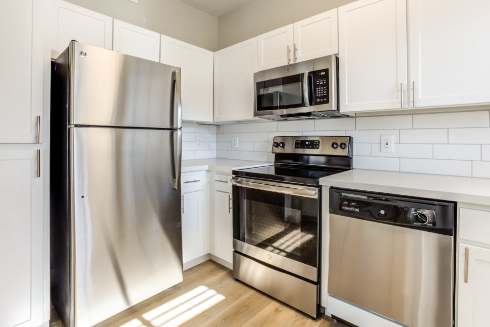 Gourmet kitchen with stainless-steel appliances and a subway tile backsplash in an apartment home at Finisterra in Tempe, Arizona