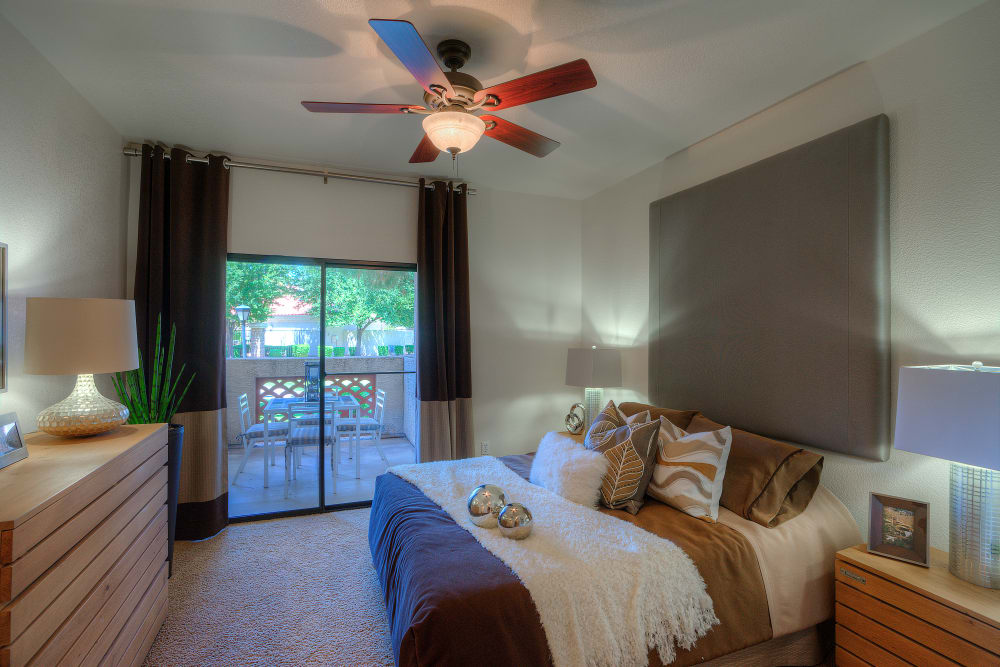Large master bedroom with ceiling fan and beautiful furnishings in model home at San Cervantes in Chandler, Arizona