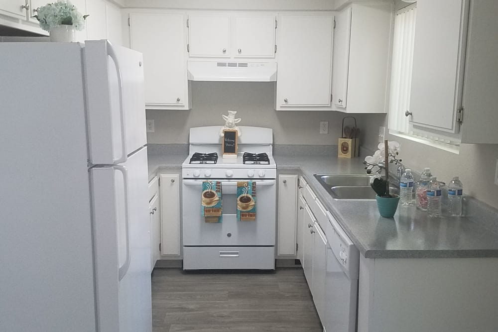 Modern kitchen with granite countertops and white appliances in model home at Sienna Heights Apartment Homes in Lancaster, California