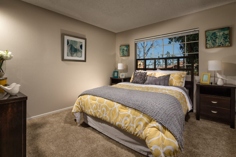 Comfy bedroom with carpet at Sierra Heights Apartments in Rancho Cucamonga, California