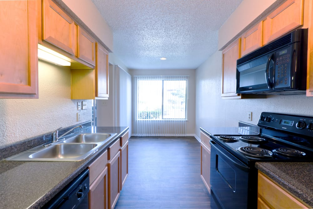 The Belmont showcase a modern home's kitchen with black appliances in Grand Prairie, Texas