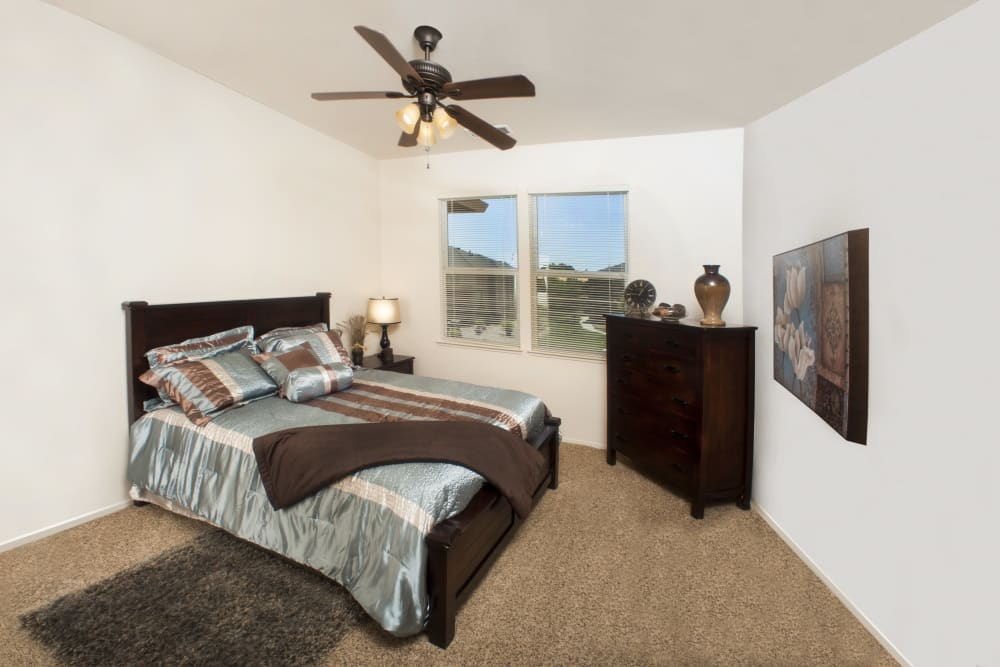 Modern bedroom with a ceiling fan at Villa Risa Apartments in Chico, California