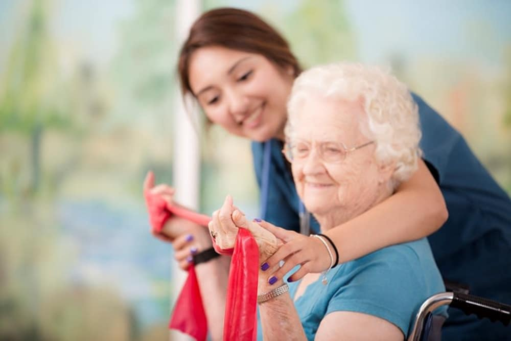 A caretaker helping a resident with strength training at The Mansions at Sandy Springs Assisted Living and Memory Care in Peachtree Corners, Georgia
