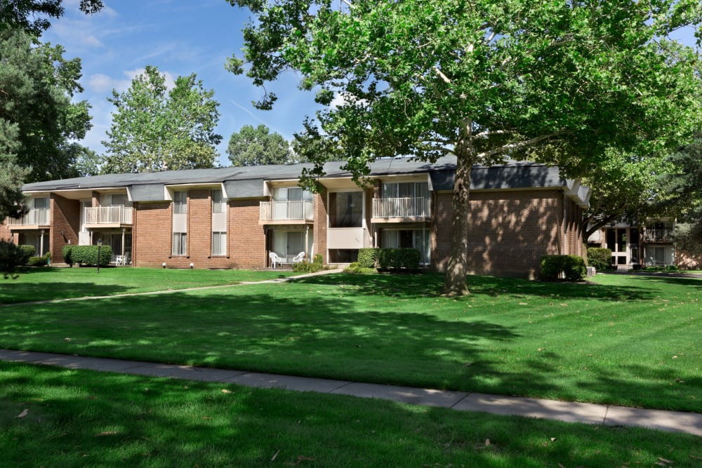 Green lawns and mature trees amid resident buildings at Kensington Manor Apartments in Farmington, Michigan