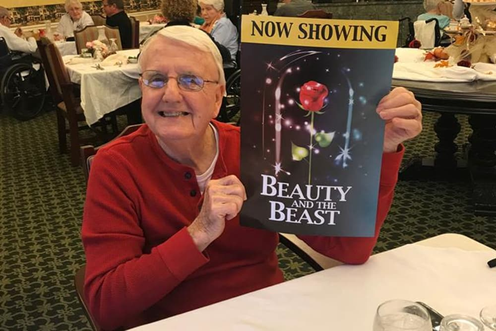 A resident holding a Beauty and the Beast play poster at West River Health Campus in Evansville, Indiana