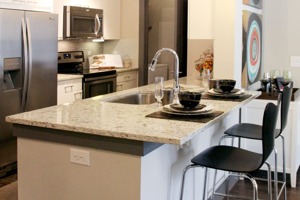 Kitchen with breakfast bar at Axis at Wycliff in Dallas, Texas