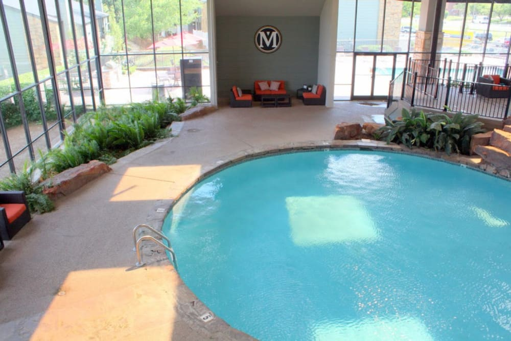 Indoor swimming pool with deck and lounge chairs at Goldelm at Metropolitan in Knoxville, Tennessee