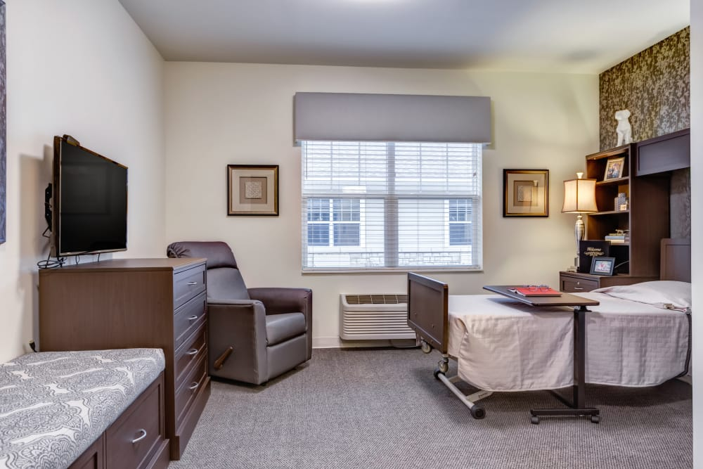 A bed and seating in a studio apartment at The Springs at Stony Brook in Louisville, Kentucky