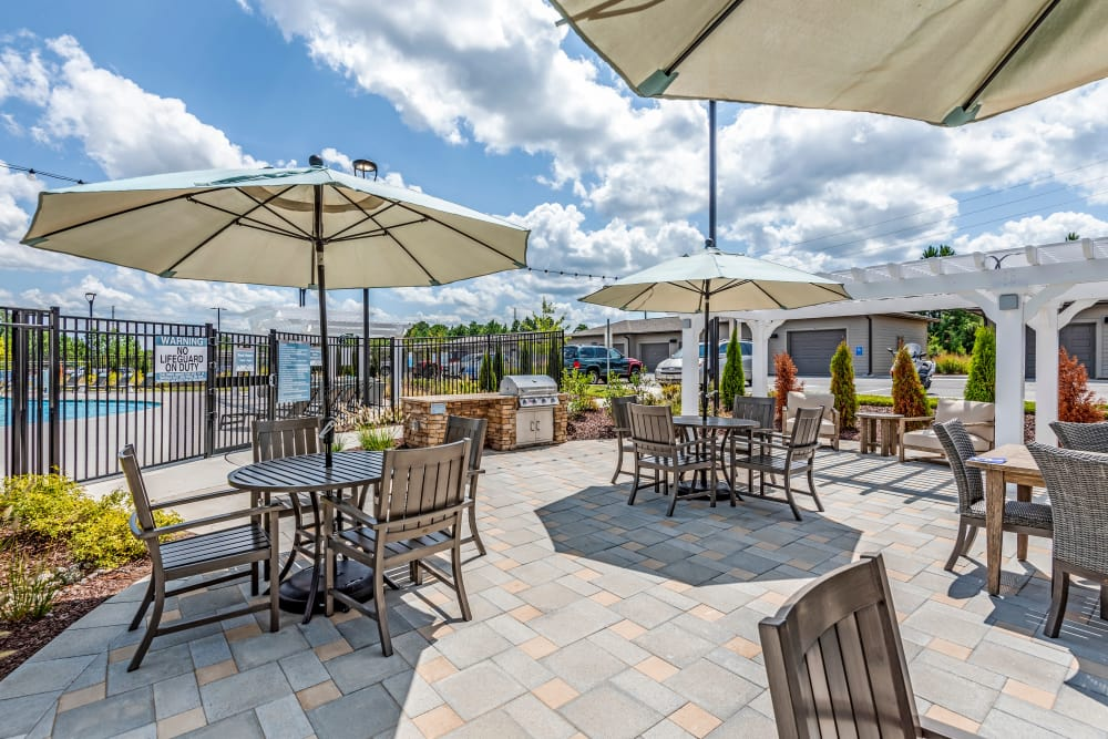 Extensive poolside seating area with umbrellas at Flats At 540 in Apex, North Carolina