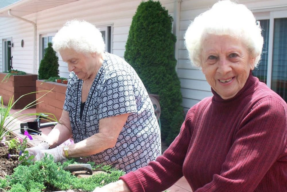 Two residents gardening, one looking at the camera at Heritage Hill Senior Community in Weatherly, Pennsylvania