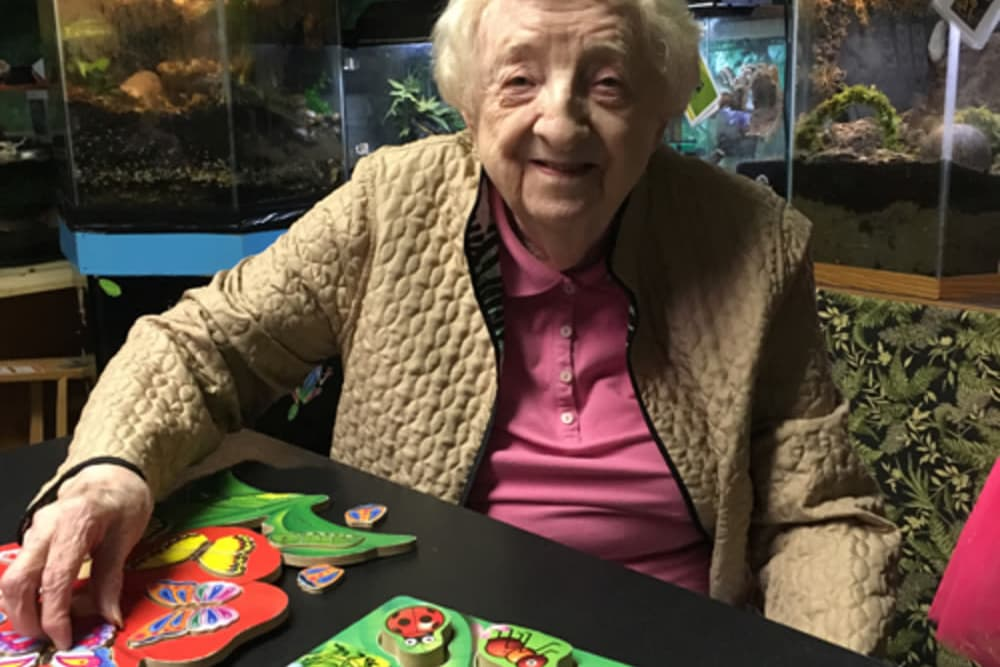 resident sitting with art looking at the camera at Heritage Hill Senior Community in Weatherly, Pennsylvania