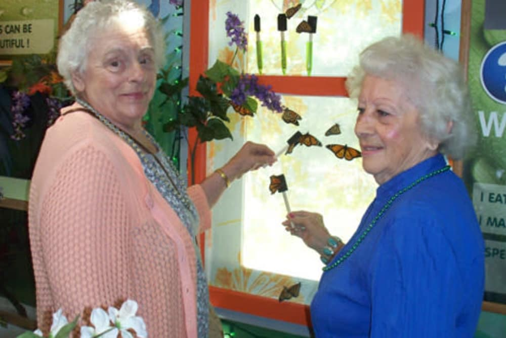 two residents from Heritage Hill Senior Community holding butterfly models in Weatherly, Pennsylvania