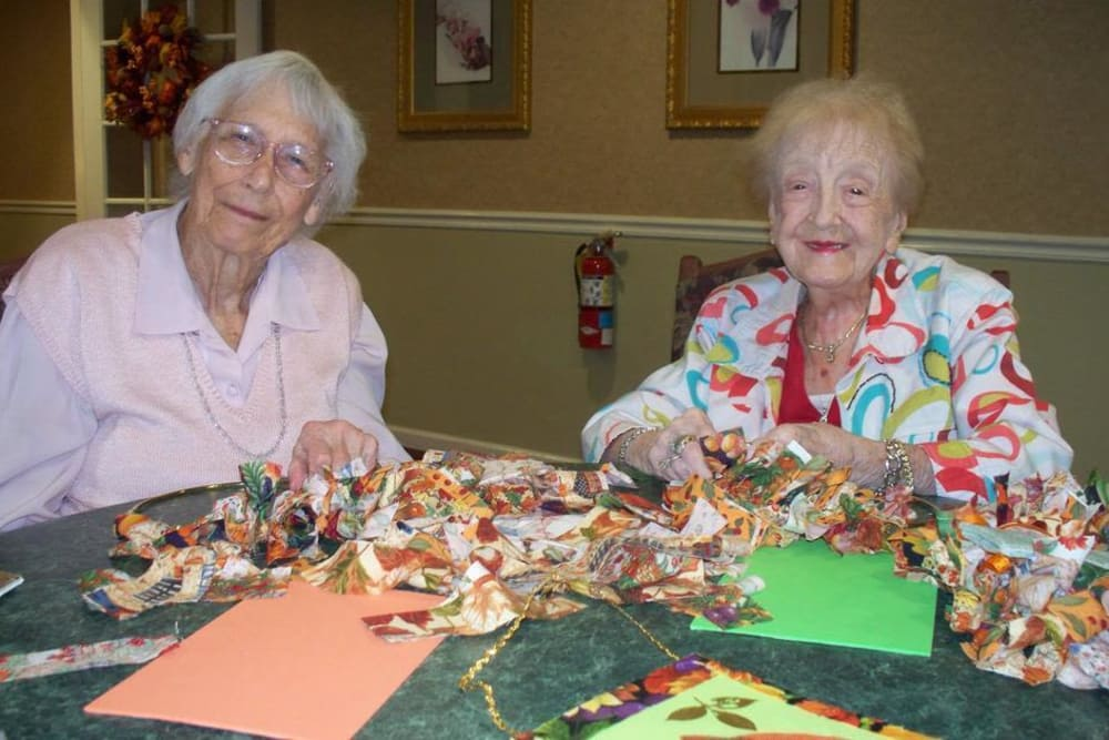 Two residents with ribbons sitting on the table in front of them at Heritage Hill Senior Community in Weatherly, Pennsylvania