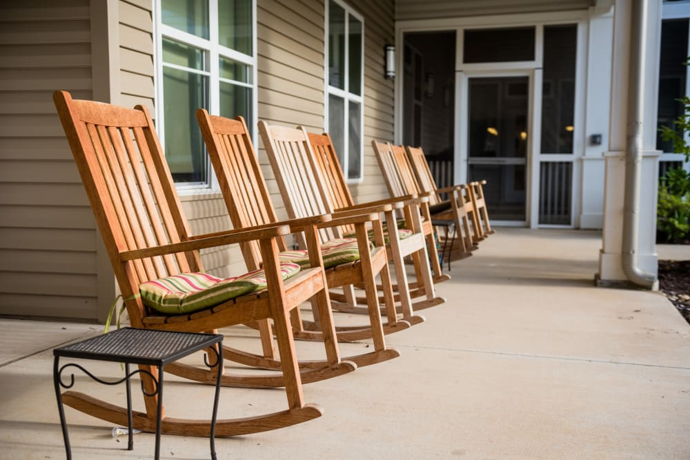 Outdoor rocking chairs at Avenir Memory Care at Fayetteville in Fayetteville, Arkansas